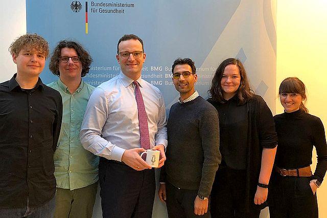 Die Macher des Übergabe-Podcasts posieren mit Bundesgesundheitsminister Jens Spahn im Bundesministerium für Gesundheit für ein Gruppenfoto.