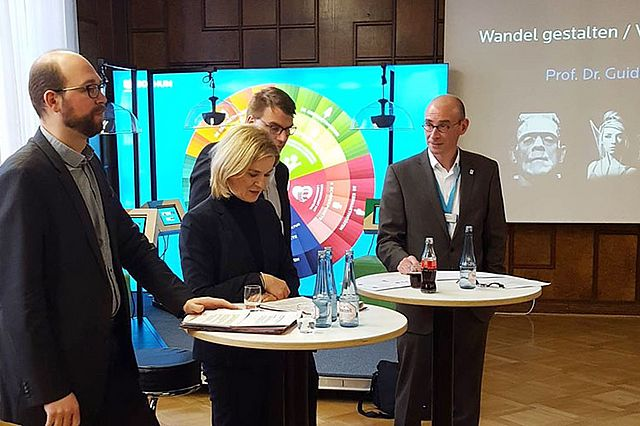 Quelle: Stadt Bochum, v.l.n.r. Sebastian Kopietz, Dr. Eva-Maria Hubbert, Prof. Dr. Guido Möllering (verdeckt) und Peter van Dyck