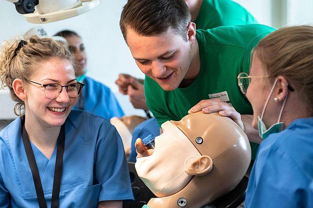 Zahnmedizinstudierende üben an einem Phantomkopf den Umgang mit Bohrer und Sauger.