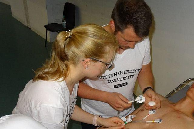 Marvin Scholten und Ann-Kathrin Laberer legen bei der Praxisaufgabe ein 12-Kanal-EKG an.