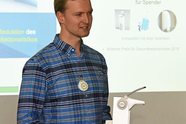Tobias Gebhardt (Gründer von GWA Hygiene) präsentiert seinen innovativen Desinfektionsmittelspender.